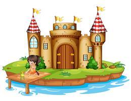 En tjej som sitter med en groda framför ett slott