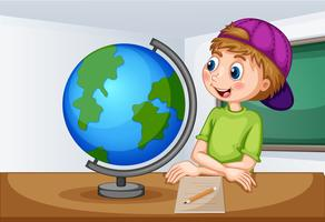 Boy looking at globe in classroom