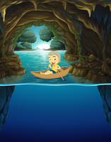Rapaz pequeno barco a remo na caverna