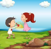 Un niño haciendo una propuesta de matrimonio en la orilla del río.
