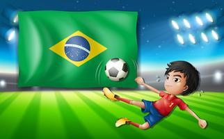 Jogador de futebol de menino na frente da bandeira do Brasil
