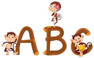 Macaco bonito e alfabeto de madeira