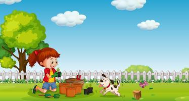 Ein Mädchen, das am Garten mit Hund pflanzt