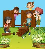 Enfants fixant une clôture dans le jardin