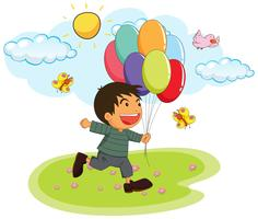 Little boy holding balloons in the park