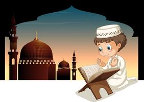 Muslim boy praying with mosque background