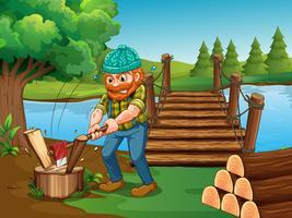 Mann, der Holz durch den Fluss hackt