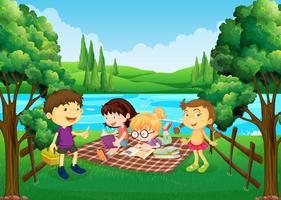 Niños haciendo picnic junto al río.