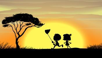 Silhouette kids running in the field