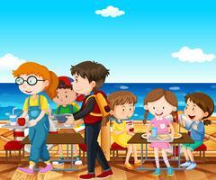 Niños almorzando junto al mar.