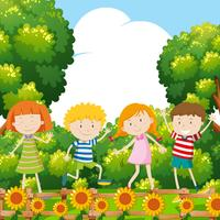 Vier kinderen in zonnebloemtuin