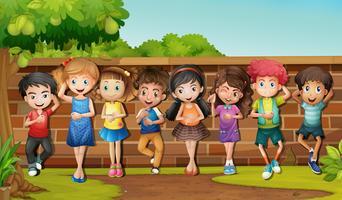 Molti bambini in piedi vicino al muro