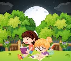 Girls reading book in park at night