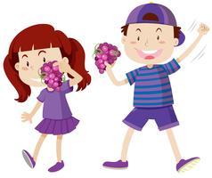 Jongen en meisje in paarse holdingsdruiven