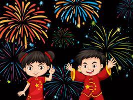 Duas crianças chinesas com fundo de fogo de artifício