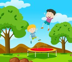 Two boys bouncing on trampoline in the park