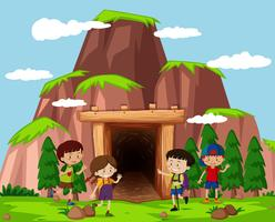 Lyckliga barn framför grottan