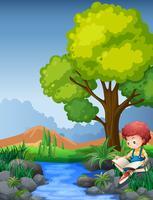 Petit livre de lecture de garçon au bord de la rivière