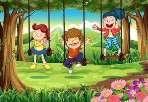 Tres niños en columpios en el bosque