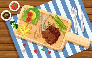Lambchop e insalata sul bordo di legno