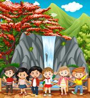 Lyckliga barn som besöker vattenfall