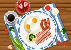 Huevos y tocino en el plato con bebidas al lado.