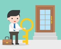 Empresario y llave grande de pie delante de la puerta de la tienda