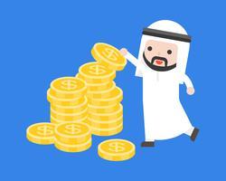 El hombre de negocios árabe lindo puso monedas de oro en la pila de dinero