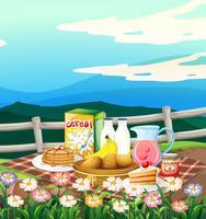 Scène met ontbijt dat op picknickdoek wordt geplaatst