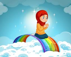 Menina muçulmana rezando sobre o arco-íris