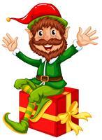 Un elfe assis sur une grosse boîte-cadeau