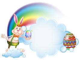 Ein Häschen, das ein Ei nahe dem Regenbogen hält