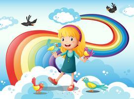 A girl and a group of birds in the sky near the rainbow