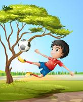A boy playing soccer at the road
