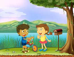 A young boy holding a bike and a girl near a wooden mailbox