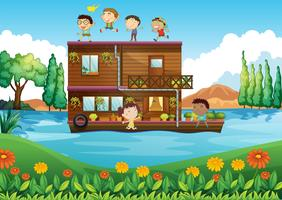 A wooden house in the middle of the river with kids
