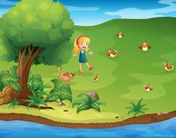Una niña con un perro y gallinas cerca del río.
