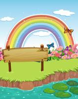 Uma tabuleta de madeira vazia na beira do rio e um arco-íris no céu