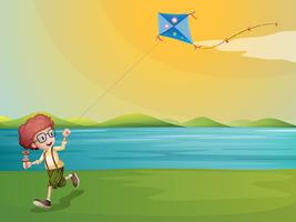 A young boy playing with his kite at the riverbank