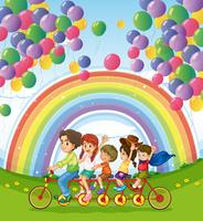 A multi-wheeled bike below the floating balloons near the rainbow