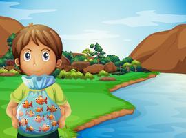 Un jeune garçon au bord de la rivière tenant un plastique plein de poissons