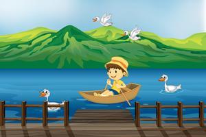 Een jongen die op een houten boot berijdt