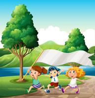 Crianças correndo perto da margem do rio, trazendo um banner vazio