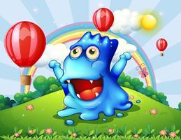 Un feliz monstruo azul en la cima de la colina con los globos flotantes.
