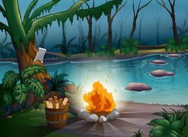 Een rivier en een kampvuur in een jungle
