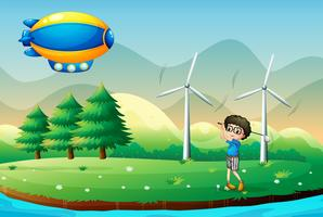 A boy playing golf in the field with windmills