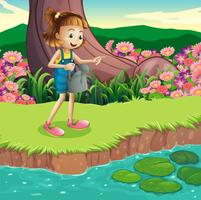 A young girl standing at the riverbank holding a sprinkler