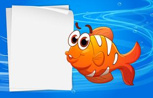 An orange fish beside an empty paper under the water