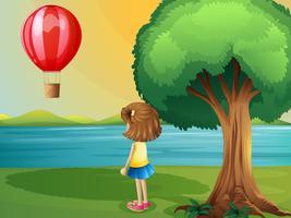 Una niña mirando el globo aerostático en la orilla del río