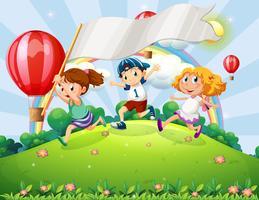 Niños con una pancarta vacía corriendo en la cima de la colina con un arco iris